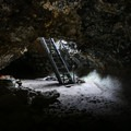 A steel stairway reaches the interior of a lava tunnel.- Lava Beds National Monument