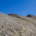 A hiker resting on the top of Deseret Peak.- Deseret Peak Hike