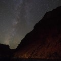 The milky way mirrors the river at night overhead.- The Grand Canyon of the Colorado River
