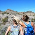 Hikers point out prominent volcanic peaks on the horizon.- Petroglyph Canyon