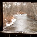 Looking through a covered bridge window at the Mills River.- Mills Riverside Park