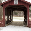 The covered bridge serves as an entrance to the park.- Mills Riverside Park