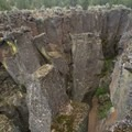 Columns have split in the fissure.- Crack In The Ground