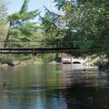 Shortly after putting on you will pass below a footbridge accessing the Pepperbox Wilderness.- Beaver River Canoe Trail