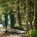 Vault toilet at Tamihi Creek East Recreation Site Campground.- Tamihi Creek East Recreation Site Campground