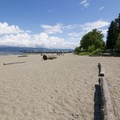 Logs set up as benches/picnic areas along the beach.- Jericho Park