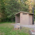 A vault toilet at the entrance to Beauty Creek Campground.- Beauty Creek Campground