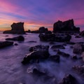 Colorful skies over the rocky coast of the hidden cove.- Roads End State Recreation Site
