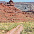 Mexican Hat seen from the less-traveled road behind it.- Mexican Hat Rock