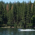 A boat races across Lake Briton.- McArthur-Burney Falls Memorial State Park