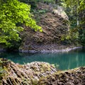 Twisting columnar basalt meets the emerald waters of the Molalla River.- Day Use Site 11: Molalla River Swimming