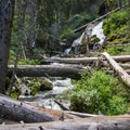 The trail crosses clear glacial runoff from the mountains at the foot of an unnamed waterfall.- Seven Devils: Windy Saddle to Sheep Lake
