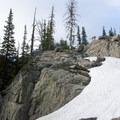 A mountain goat looks down from the rocks above camp.- Seven Devils: Windy Saddle to Sheep Lake