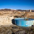 A cattle trough sits beside a stone tub that lies away from the source allowing water to cool slightly.- Kyle Hot Springs