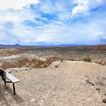 A bench with a panoramic view overlooking the park at the end of the Eagle Point Trail.- Cathedral Gorge State Park
