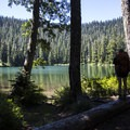 A hiker stops to enjoy the view of crystal clear Soda Peaks Lake.- Soda Peaks Lake