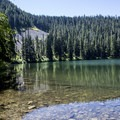Clear blue waters of the lake reflect the shadows of the ridge above.- Soda Peaks Lake