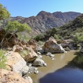 A swimming hole in a scenic riverbed.- Red Rock Pool