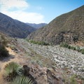 A view of a year-round river flowing through a dry valley environment.- Bridge to Nowhere / East Fork San Gabriel River Trail