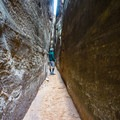 The Joint Trail looks like a slot canyon, but it is actually a narrow path between two enormous boulders. This section provides some amazing and different scenery from the rest of the hike. - The Needles