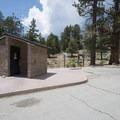 Vault toilet facility at the Woodland Trailhead.- The Woodland Interpretive Trail