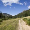 The trail meanders along a gravel track through meadows alongside Cow Creek.- Bridal Veil Falls via Cow Creek Trail