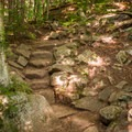 Natural stone steps augment the trail in places.- Cascade + Porter Mountains