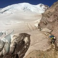 Climbers skirt an open crevasse while the summit looms high above.- Mount Rainier: Emmons-Winthrop Glacier Route