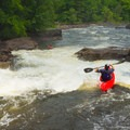 A paddler boofs into the lower slide on Colton Falls.- Raquette River: Stone Valley
