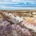 Top view of multicolored layers with wind turbines in the distance.- Paint Mines Interpretive Park