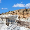 Hikers on the trail leading above the hoodoos.- Paint Mines Interpretive Park