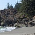 A woman climbs the rocks to leave the beach.- Secret Beach