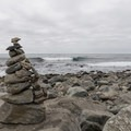 A cairn sits along the rocky coastline at Willow Creek Beach.- Willow Creek Beach + Picnic Area