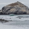 Waves crash with San Martin Rock in the background.- Willow Creek Beach + Picnic Area