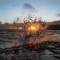 A wave splashes against a rock during sunset.- Davenport Landing Beach