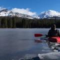 Kayaking during the winter requires breaking some thin ice. Manzanita Lake, Lassen Volcanic National Park.- Manzanita Lake