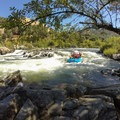 A raft plunges into the beginning of Troublemaker.- South Fork of the American River: Chili Bar to Coloma