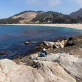 A hiker rests and enjoys the view of Missionary Beach.- Granite Point + Moss Cove Trails