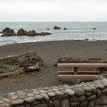 A stone wall borders the parking lot.- Wilson Creek Beach + Picnic Area