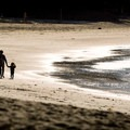 A family goes for a stroll down an otherwise empty beach at Halfmoon Bay.- Halfmoon Bay