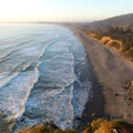 The several-mile-long Crescent Beach curving toward Crescent City.- Crescent Beach Overlook