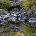 Reflections of the trail in a puddle created by a small stream.- Bear Basin + Seven Up Pass