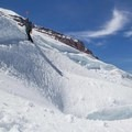 A climber cautiously navigates a crevasse, on belay, descending the Emmons Glacier.- Mount Rainier: Emmons-Winthrop Glacier Route