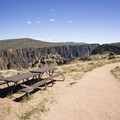 Picnic tables on the edge of a cliff at Pulpit Rock in Black Canyon of the Gunnison.- South Rim Road