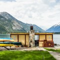 Boat house with kayaks and a fire pit for smores at the end of your day of adventure.- The North Cascades Lodge at Stehekin