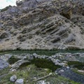 The long narrow pool lies at the base of the canyon cliffs.- Twelve-Mile Hot Spring