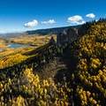 Aerial view of Silver Jack Reservoir surrounded by ridges and hillsides covered in aspen.- Owls Creek Pass + Silver Jack Reservoir