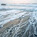 The sun illuminates a section of thin fog over the ocean.- Enderts Beach