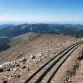 View south from the summit of Pikes Peak (14,115 ft) with the old cog railway.- Pikes Peak Summit + Highway