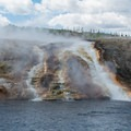 Steaming spring water entering the Firehole River.- Grand Prismatic Spring + Midway Geyser Basin